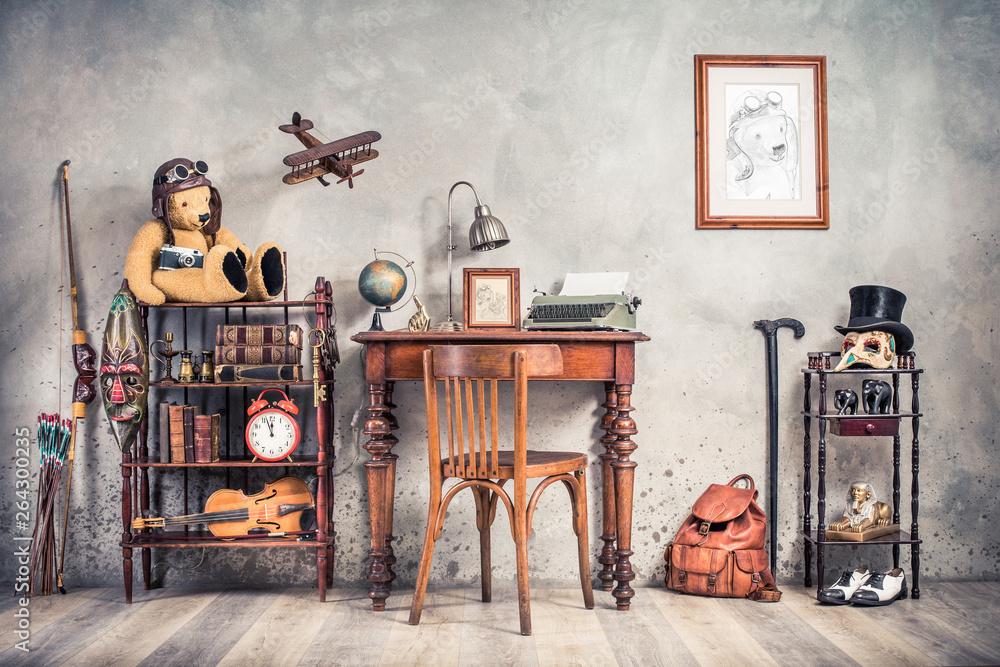 Fototapeta Vintage old typewriter, lamp, frame, forefinger on antique table, chair, Teddy Bear with photo camera, retro clock, books, fiddle, keys on shelf, plane, mask, cylinder hat, shoes, cane, backpack, bow