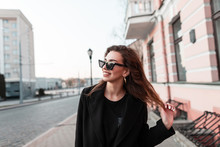 Funny Attractive Happy Young Hipster Woman With A Positive Smile In A Fashionable Black Coat In Stylish Dark Sunglasses Stand Near A Vintage Building Outdoors. Urban Joyful Girl Model. Street Style.