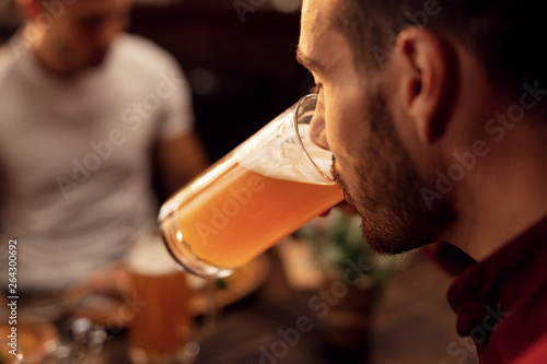 Fotografia Close up of man drinking beer in a bar.
