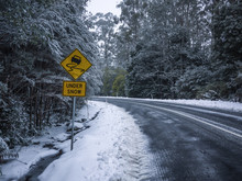 Slippery Road Warning Sign For Car Drivers On Side Of A Snow Covered Road. Icy Scenic Mountain Route In Winter Forest. Mt Donna Buang, VIC Australia