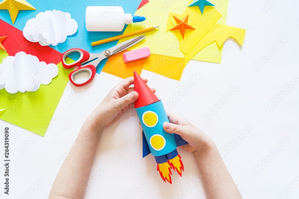 hands of the child make a paper craft rocket. Cosmos clouds and stars colored paper. The creative process