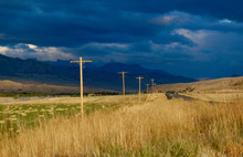 The Road To Yellowstone National Park As A Storm Forms In The Distance,  But The Sun Shines On The Telephone Poles In The Foreground.