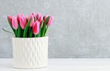 Fototapeta Tulipany - Pink tulips in white ceramic vase, grey stone background.