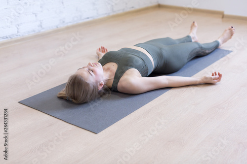 Foto Woman laying on mat in relaxing pose on the floor