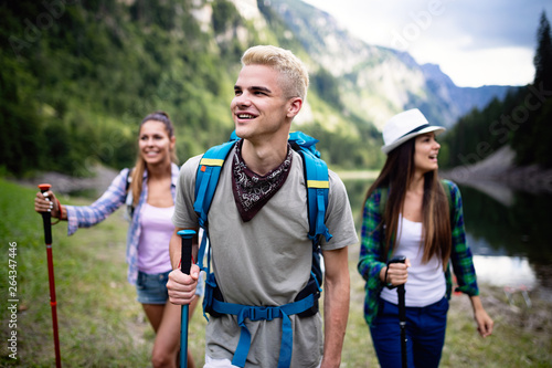 Fototapeta Group of smiling friends hiking with backpacks outdoors. Travel, tourism, hike and people concept. obraz na płótnie