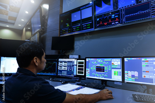 Fotografie, Obraz  Engineer looking to work in the electrical control room