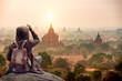 Leinwanddruck Bild The tourist sitting watching Bagan pagoda landscape view during sunrise and the ancient pagoda in Bagan,Mandalay Myanmar