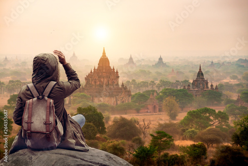 Fotografiet The tourist sitting watching Bagan pagoda landscape view during sunrise and the