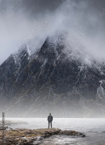 Foto auf AluDibond Rosa dunkel Man stood in front of foggy misty mountain to give scale of mountain size and concept of overpowering challenge