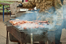 Cooking Grilled Meat. Servicemen Prepare Barbecue. A Man In A Military Camouflage Uniform Fry The Meat. Rest Of The Military At The Festival. Army Cuisine At The Training Ground.
