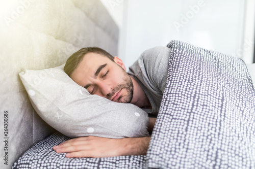 Foto  Handsome young man sleeping in bed at home