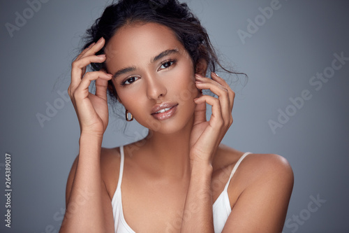 girl touching her face and looking to camera