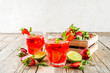 Homemade strawberry lemonade with lime and mint, rustic wooden background copy space