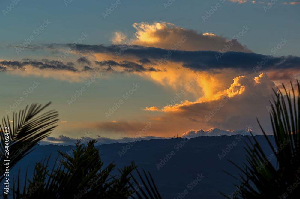 Multiple exposure of some orange and yellow clouds in a sunset over the Andean mountains of central Colombia.