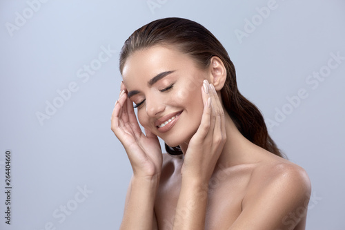 Obraz happy woman touching her face, girl smilling with close eyes, healthy happy face - fototapety do salonu