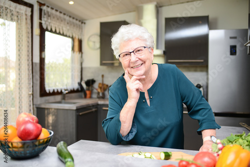 Fototapeta happy senior active woman cooking at home in a modern kitchen obraz