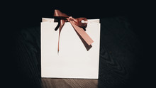 Small White Paper Bag With Pink Bow On Black Background On Wood Floor.