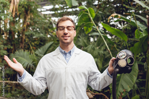 Photo  smiling handsome scientist in white coat and glasses with closed eyes holding ru