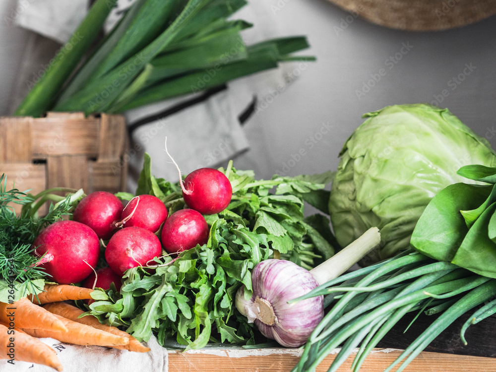 Fototapeta Spring vegetarian food ingredient variety. Assortment of spring vegetables for healthy cooking over rustic cupboard, white wall background. Healthy vegetarian vegan food from the local market