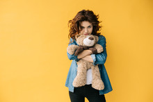 Upset Curly Redhead Young Woman Holding Teddy Bear On Orange