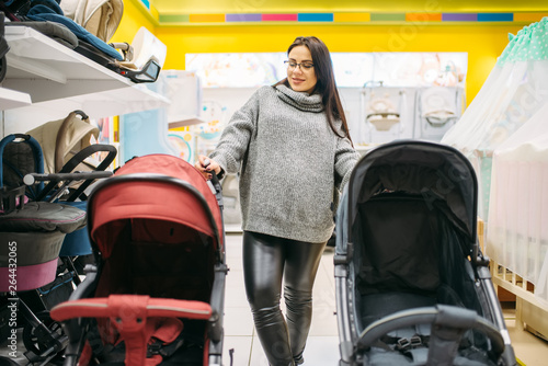Fototapety, obrazy: Pregnant woman looking for pushchair in store