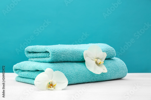 Stack of soft clean towels with beautiful flowers on table against color background Wallpaper Mural