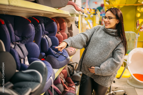 Fotografía  Pregnant woman choosing child car seat in store