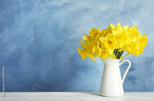 Fotografie, Obraz Bouquet of daffodils in jug on table against color background, space for text