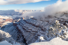 Grand Canyon In Winter, Viewed From The South Rim. Snow Covers The Canyon Walls. Clouds Clinging To The Canyon, And Overhead In The Blue Sky. Edge Of The Rim And Bushes Covered With Snow.