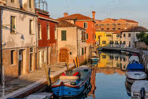 Sunset at a Small Canal - Sunset view of a narrow, old, but colorful canal on Murano Islands. Venice, Italy. No trademark, logo, or person in the image.