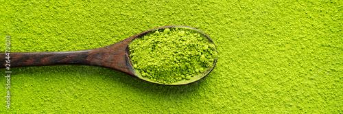 Odgórny widok drewniana łyżka z zieloną herbatą Matcha na prochowym maccha tekstury tle. Długi szeroki baner z miejsca na kopię.