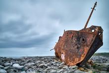 Rusty Boat Tilts On Rocks