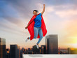 super power and people concept - happy african american young woman in superhero red cape jumping on roof top over sunset in tokyo city background