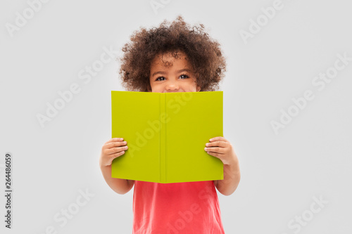 Fotografie, Obraz  childhood, literature and reading concept - happy little african american girl w