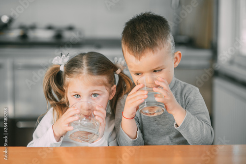Children boy and girl in the kitchen drinking water from glasses Fototapete
