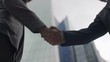 Two Asian business men's hands come together for a handshake in the city, in slow motion