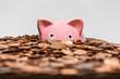 Leinwanddruck Bild - Pink piggy bank drowning in ocean of copper pennies.
