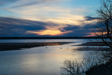Bemidji, Minnesota, The 2018 Best Town In Minnesota Is Seen Across Lake Bemidji And Snow Geese Swim Where The Mississippi River Flows Toward The Camera At Sunset On A Beautiful Evening.