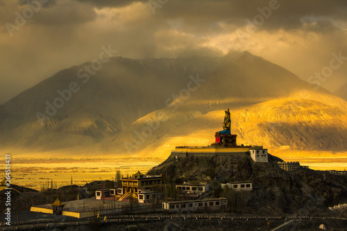 The Maitreya Buddha statue with Himalaya mountains in the background at sunset from Diskit Monastery, Nubra valley, Leh Ladakh, Northen India Canvas Print