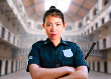 Young Serious And Attractive Asian American Guard Woman Standing At State Penitentiary Prison Hall Wearing Police Uniform In Crime Punishment
