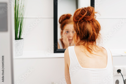 Bleary eyed woman peering at herself a the mirror Canvas Print