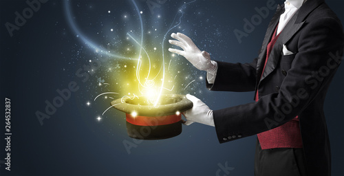 Magician hand conjure with wand  light from a black cylinder Fototapet