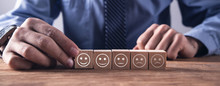 Man Showing Wooden Cube. Rating Satisfaction. Feedback In Form Of Emotions.
