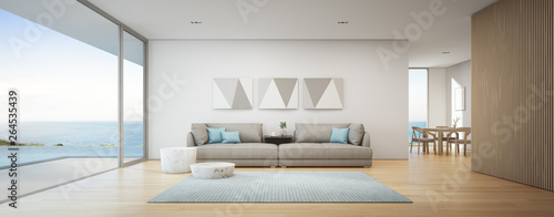 Fototapeta Sea view dining and living room of luxury summer beach house with swimming pool near wooden terrace. Big gray sofa in vacation home or holiday villa. Hotel interior 3d illustration. obraz