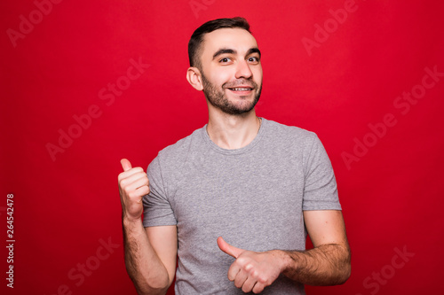 Valokuva  Portrait of a happy young man i pointing fingers away at copy space isolated ove