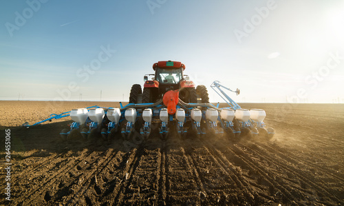 Farmer with tractor seeding soy crops at agricultural field Canvas Print