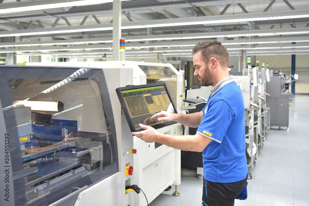 Fototapeta Arbeiter in der Mikroelektronik bedient moderne Maschine zur Fertigung von Bauteilen - Automatisierung in der Industrie // Workers in microelectronics operate modern machines for manufacturing compone