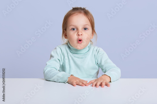 Image of astonished lovely little sitting at white desk, small
