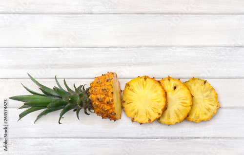 Photo  Fresh tropic fruit pineapples with slices on background of white painted wooden planks with space for text