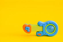 Toy Guitar Isolated On A Yello...